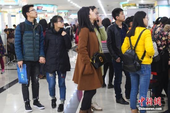 资料图:2017年3月8日,山西太原举行女性专场招聘会,现场有不少男士陪同前来,帮忙挑选工作。中新社记者 武俊杰 摄