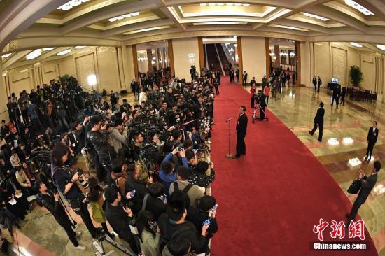 """3月8日,十二届全国人大五次会议举行第二次全体会议,""""部长通道""""受到众多记者关注。中新社记者 金硕 摄"""