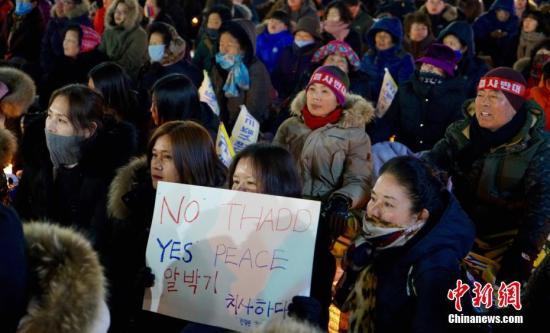 """3月8日晚,在距离""""萨德""""部署地韩国星州高尔夫球场最近的城市金泉市,上千民众冒雪集会,抗议部署""""萨德""""。这也是该市民众在韩美宣布部署""""萨德""""后举行的第200次集会。 <a target='_blank' href='http://www.chinanews.com/'>中新社</a>记者 吴旭 摄"""