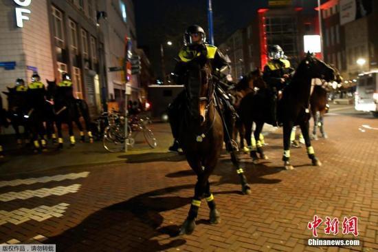 """当地时间3月11日,人们聚集在位于荷兰鹿特丹的土耳其领事馆外,抗议荷兰政府禁止土外长飞机入境。荷兰政府当日取消土耳其外长恰武什奥卢班机在荷兰的着陆权。荷兰外交部发表声明称,取消土外长班机着陆许可是出于""""公共安全方面的原因""""。"""