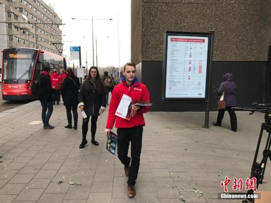 3月15日,荷兰将举行议会二院(众议院)选举。选前民调显示,参加此次选举的28个政党,无一能获得超过20%的选票。荷兰议会二院共有150个席位。图为议会选举前一天,3月14日,荷兰工党在海牙中央火车站前拉票,向支持者奉送红色的玫瑰花。中新社记者 沈晨 摄