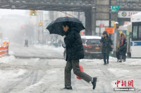 3月14日,今冬最强暴风雪施特拉(Stella)席卷美国东北部。图为行人雪中经过纽约市皇后区法拉盛街头。 /p中新社记者 马德林 摄