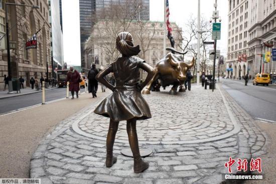 """资料图:华尔街上,""""无所畏惧的女孩""""铜像双手叉腰,面朝著名的华尔街铜牛。"""