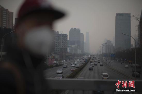 资料图:北京市民在雾霾中出行。 中新社记者 刘关关 摄