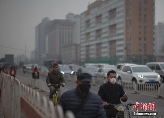 资料图 北京市民在雾霾中出行。 中新社记者 刘关关 摄