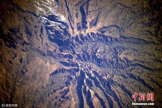 """资料图:2017年3月20日,法国宇航员Thomas Pesquet在太空执行任务期间用相机记录了从太空俯瞰到的地球景观,在他的镜头下,俄罗斯雪地好似极简主义画家笔下的抽象画;沙特阿拉伯沙漠上的灌溉盛况如绿色豌豆铺洒又似一盘盘光碟;闻名世界的美国大峡谷不再""""大得难以想象"""";阿尔卑斯山上的积雪犹如凸起的鸡蛋白。Thomas从独特视角向人们展示了地球母亲的震撼美景。图片来源:视觉中国"""