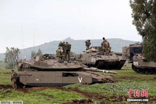 资料图:以色列陆军在戈兰高地举行演习。图为以军士兵在坦克和装甲车上休息。