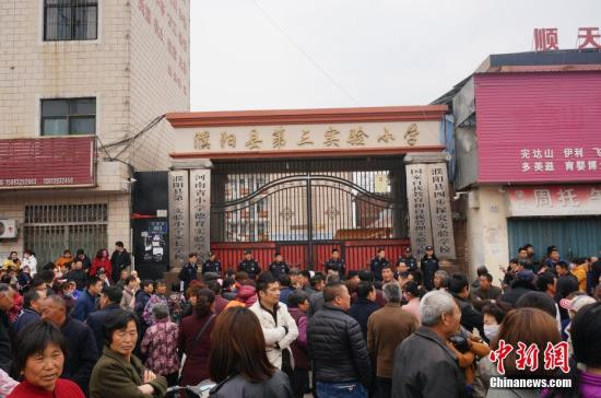 濮阳县第三实验小学校门口,聚集了很多家长及围观群众。目前该校已经停课,官方正就事故原因进行详细调查。 韩章云 摄