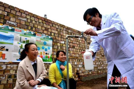 """渭源县组织水务局、环保局等单位的骨干力量深入各乡镇和水源地保护点检测水质,确保居民喝上安全卫生的""""健康水""""和""""放心水""""。图为技术人员在村民家里采取水样。 王纲 摄"""