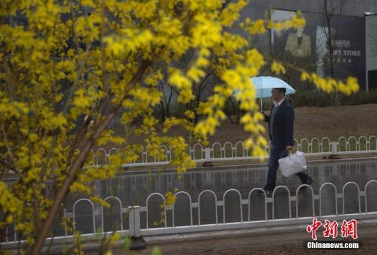 3月24日,北京民众在雨夹雪天气中出行。雨夹雪和大降温减缓了北京入春的步伐。 <a target='_blank' href='http://www.chinanews.com/'>中新社</a>记者 刘关关 摄