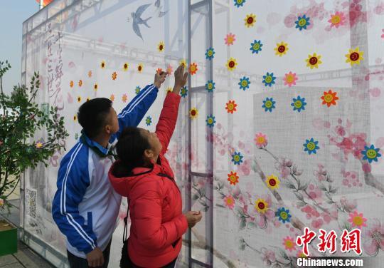 市民在寄语百花墙上贴上花朵表达思念。 张瑶 摄