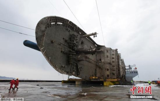 """当天下午4时55分,""""世越""""号向所在海域东南方向3公里处,即半潜船所在的安全水域移动。25日凌晨4时10分,""""世越""""号沉船被抬至半潜船上,这意味着打捞工作基本取得成功。"""