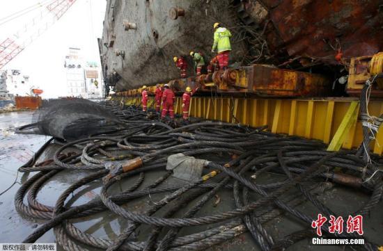 """当地时间3月27日,韩国珍岛工人正在移除""""世越号""""船体上的电线。日前沉没近3年的韩国""""世越号""""船体已经被抬出水面。"""