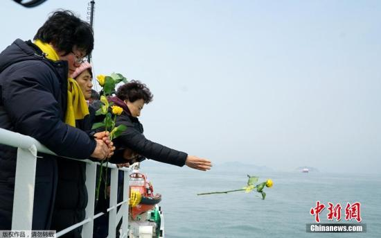 """当地时间2017年3月28日,韩国珍岛,民众悼念""""世越""""号遇难者。为将""""世越""""号沉船运至木浦新港,打捞组正加速进行排水和除油工作。"""