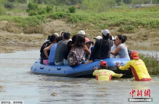 当地时间2017年3月31日,秘鲁北部Piura,当地民众在洪水中转移。近日,南美国家秘鲁遭遇了由暴雨引发的洪水和泥石流灾害。目前已造成至少98人死亡,近百万人受灾。