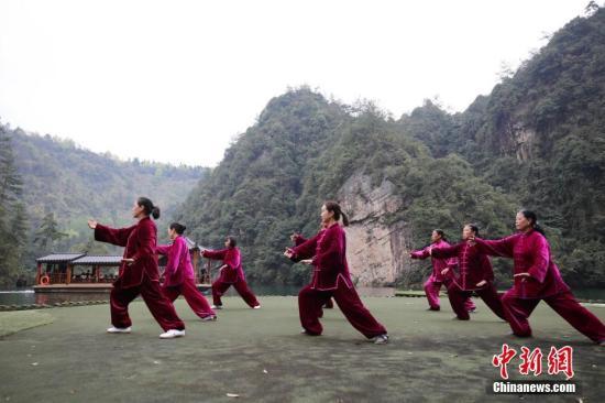 资料图:太极爱好者在湖南张家界宝峰湖风景区练习太极,畅享健身带来的快乐和健康。吴勇兵 摄
