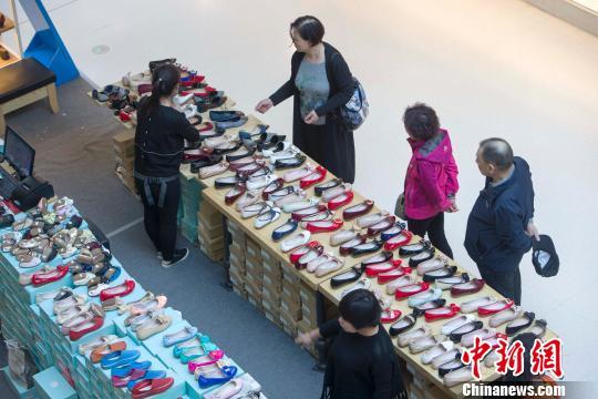 资料图:民众正在商场选购鞋子。 张云 摄