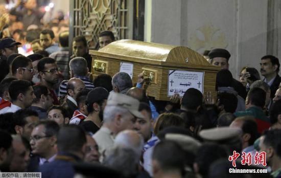 """坦塔市民众抬着为遇难者准备的棺材,参加葬礼。9日晚些时候,极端组织""""伊斯兰国""""通过其控制的社交媒体宣布对坦塔市和亚历山大市的教堂袭击事件负责。"""