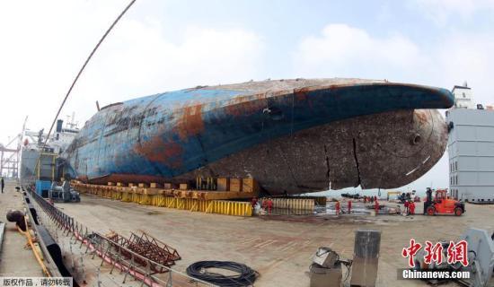 """据韩媒报道,当地时间9日17时35分,韩国 """"世越""""号沉船成功上岸,运送过程历时约8个半小时。图为当地时间4月1日,在韩国木浦港,被打捞出水的""""世越""""号沉船等待被移送上岸。"""