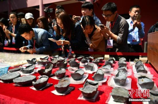 图为民众围观考古发掘出的文物。 刘忠俊 摄