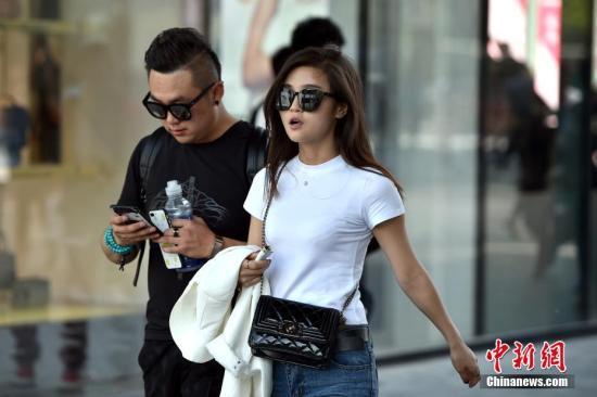 图为北京三里屯街头的姑娘小伙们换上夏装出行。 记者 金硕 摄