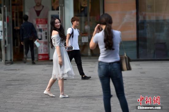 """4月14日,北京市内天气晴朗,午后受对流扰动影响,浮云增多,转为多云天气。今天空气流动性逐渐增强,大气透明度和能见度有所改善,天气条件比较利于户外活动和交通出行。明天白天,北京地区在高空西北气流控制下,气温将显著升高,明天最高气温将达29℃,恍如""""初夏""""。图为北京三里屯街头的姑娘小伙们换上夏装出行。 记者 金硕 摄"""