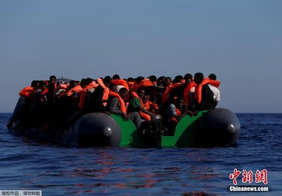 资料图:当地时间2017年4月14日,利比亚Zawiya附近海域,移民从乘坐的橡皮艇落水后浮在水面上。