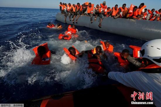 当地时间2017年4月14日,利比亚Zawiya附近海域,移民从乘坐的橡皮艇落水后浮在水面上,非政府组织移民海上援助站救助移民,134名移民全部获救。