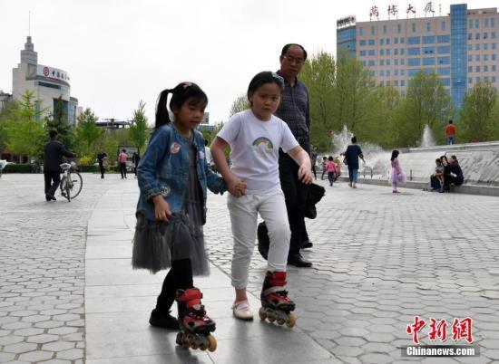 4月15日,河北雄县一广场,两个孩童穿一双轮滑鞋玩耍。 <a target='_blank' href='http://www.chinanews.com/'>中新社</a>记者 翟羽佳 摄