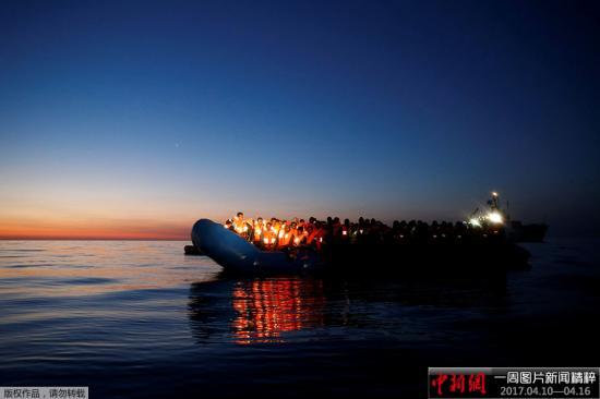 资料图:2017年4月15日,地中海的黎明里,一艘等待被救援的难民船飘在海上。