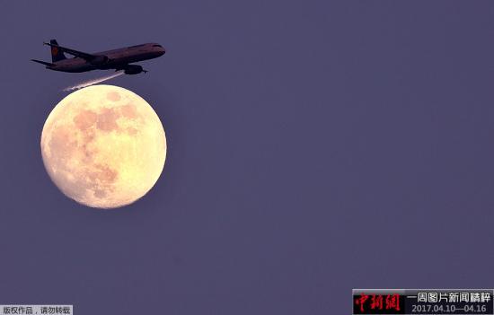 资料图:客机从月亮前飞过。