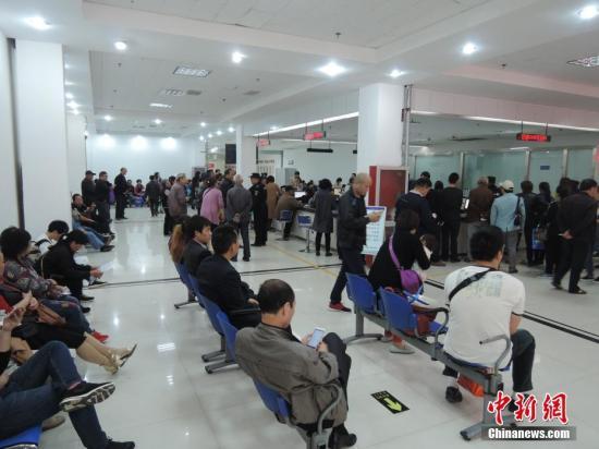 """4月17日,星期一,记者在郑州市社会保险办事大厅看到,被网友调侃为""""跪式窗口""""的服务窗口已经整改。此前将工作人员与市民阻隔开的玻璃围栏已经撤掉,服务台三面呈开放式,办事大厅里的叫号机重新启用,并增派工作人员维持秩序,组织市民有序排队。但是,记者也注意到,由于前往办理业务的市民太多,现场环境嘈杂,对于安放在服务窗口前的座椅,市民多不愿意坐,仍有不少人宁愿扭着身子趴在服务台上和工作人员近距离交流。韩章云 摄"""