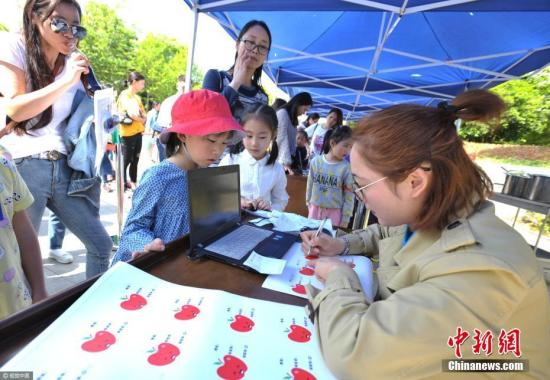 资料图:小学招生面试,数千家长烈日下排长队。图为一位参加面试的孩子在登记信息。 书童 摄 图片来源:视觉中国