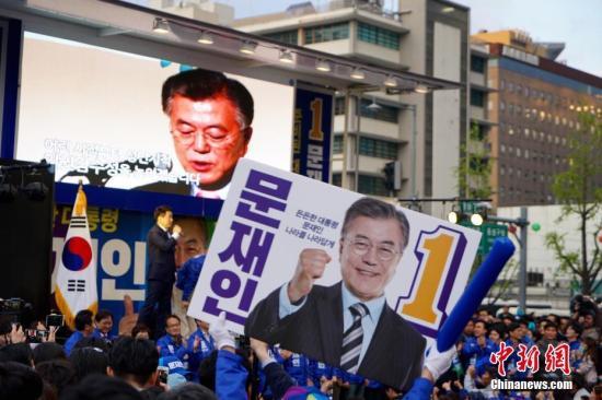 """4月17日,韩国最大在野党共同民主党总统候选人文在寅(图中)在首尔光化门广场参加竞选造势活动。韩国第19届总统选举竞选活动当日正式启动,包括国会5大党派代表在内的15名候选人将在22天的法定竞选期间奔走全国各地展开""""拉票大战""""。 记者 吴旭 摄"""