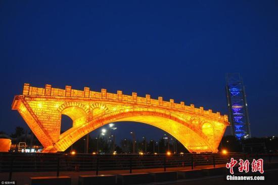 """4月18日晚,北京奥林匹克公园,新建成的""""丝路金桥""""大型景观正在试灯,呈现出金碧辉煌的醉人景致, 迎接""""一带一路""""国际合作高峰论坛的到来。 杜佳 摄 图片来源:视觉中国"""