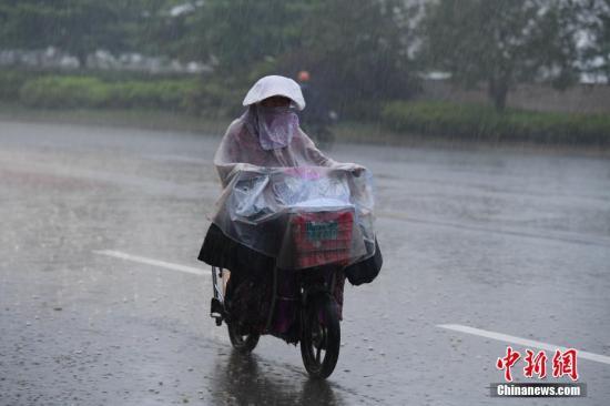 资料图:4月21日下午,福州突下大暴雨,许多路面积水成河,市民冒雨艰难出行。 王东明 摄