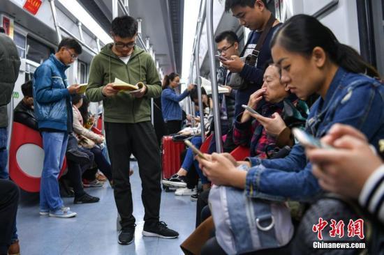 地铁上乘客在玩手机。(资料图) 中新社记者 任东 摄