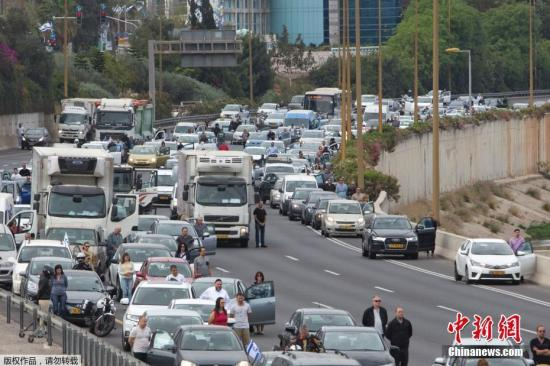 当地时间4月24日,随着纪念犹太人大屠杀的警报声响起,以色列民众纷纷停车站定,悼念纳粹大屠杀遇难者。图为以色列特拉维夫公路上,民众纷纷停车默哀。
