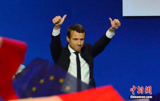 """根据法国内政部23日晚公布的部分计票结果,在刚刚结束的法国总统选举第一轮投票中,中间派独立候选人、""""前进""""运动领导人艾曼努尔・马克龙以23.11%的得票率居第一位,极右翼候选人、国民阵线主席马丽娜・勒庞以23.08%居第二位。两人将进入第二轮对决,争夺下一届法国总统宝座。马克龙当晚在巴黎举行的庆祝集会上表示,他领导的政治运动""""在一年时间内就改变了法国的政治面貌""""。图为马克龙在庆祝集会上。 <a target='_blank' href='http://www.chinanews.com/'>中新社</a>记者 龙剑武 摄"""