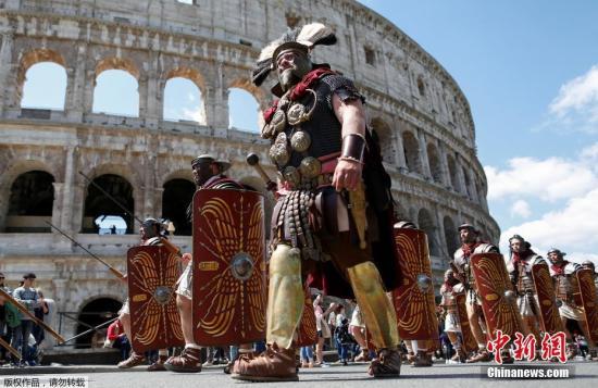 """一名""""古罗马指挥官""""带领""""士兵""""行进在罗马斗兽场前。"""