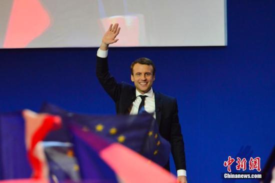 """根据法国内政部23日晚公布的部分计票结果,在刚刚结束的法国总统选举第一轮投票中,中间派独立候选人、""""前进""""运动领导人艾曼努尔・马克龙以23.11%的得票率居第一位,极右翼候选人、国民阵线主席马丽娜・勒庞以23.08%居第二位。两人将进入第二轮对决,争夺下一届法国总统宝座。马克龙当晚在巴黎举行的庆祝集会上表示,他领导的政治运动""""在一年时间内就改变了法国的政治面貌""""。图为马克龙在庆祝集会上。  <a target='_blank' href='http://www-chinanews-com.wps222.com/'>中新社</a>记者 龙剑武 摄"""