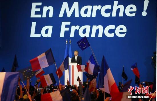 """根据法国内政部23日晚公布的部分计票结果,在刚刚结束的法国总统选举第一轮投票中,中间派独立候选人、""""前进""""运动领导人艾曼努尔・马克龙以23.11%的得票率居第一位,极右翼候选人、国民阵线主席马丽娜・勒庞以23.08%居第二位。两人将进入第二轮对决,争夺下一届法国总统宝座。马克龙当晚在巴黎举行的庆祝集会上表示,他领导的政治运动""""在一年时间内就改变了法国的政治面貌""""。图为马克龙在庆祝集会上。&#10;&#10;<a target='_blank' href='http://www.chinanews.com/'>中新社</a>记者 龙剑武 摄"""