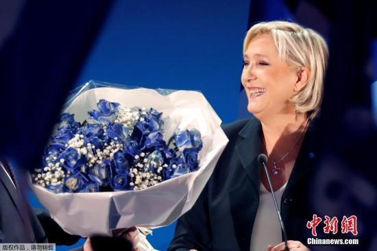 """4月23日,在法国埃南—博蒙,极右翼""""国民阵线""""主席玛丽娜·勒庞在竞选晚会上向支持者致意。法国内政部23日晚发布的初步统计数据显示,""""非左非右""""的""""前进""""运动候选人埃马纽埃尔·马克龙和极右翼政党""""国民阵线""""候选人玛丽娜·勒庞在当天举行的法国总统选举首轮投票中得票领先,将进入法国总统选举第二轮投票。"""