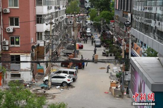 """近日,北京市朝阳城管三里屯执法队对同里地区42号楼进行了开墙打洞整治工作,本次行动共整治33家商户,拆除面积为1000平方米。这条街全长200多米,是连接太古里南区及北区的一条商业街,因为脏乱吵曾被称为""""脏街"""",周边部分居民和商户存在擅自改变住房结构、转租转借、私搭乱建""""棚亭阁""""、私自破墙开门、无照经营、违规设置广告牌等违法现象。<a target='_blank' href='http://www.chinanews.com/' >中新网</a>记者 金硕 摄"""