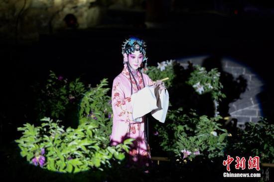 """4月26日晚,园林版昆曲《牡丹亭》在北京圆明园含经堂遗址牡丹丛中上演。时值含经堂万株牡丹花期,此番世界级皇家园林与昆曲的携手演绎的""""园林+戏曲""""的首度跨界组合,也为现场观众带来一场鲜活的文化体验。<a target='_blank' href='http://www.chinanews.com/'>中新社</a>记者 崔楠 摄"""