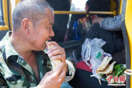 近日,在杭州一条马路上,来自山东临沂的几位农民工正在吃自己的午餐。 图片来源:视觉中国