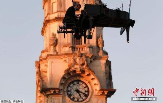 资料图:巴西圣保罗市,钢琴师悬吊在半空中表演弹琴。