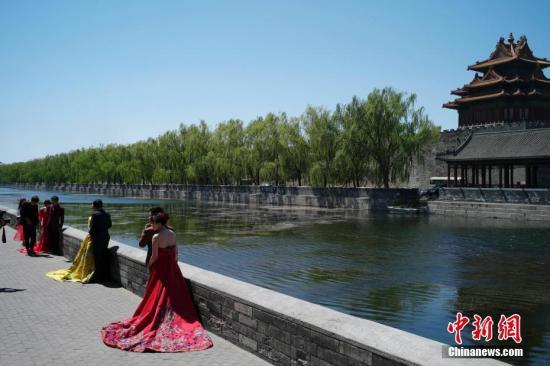 资料图:4月27日,北京天气晴好,情侣在故宫外拍摄婚纱照。中新社记者 盛佳鹏 摄