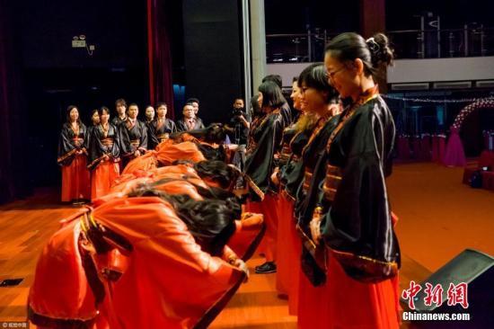 """资料图片:2017年4月25日,北京某国际学校2017届高三学生成人礼,数百名高三学生在家长的陪伴下走上红地毯跨过""""成人门"""",以中西合璧式的毕业仪式,开启同学们奔赴美国、英国和加拿大等西方国度的本科留学生涯。詹敏 摄 图片来源:视觉中国"""