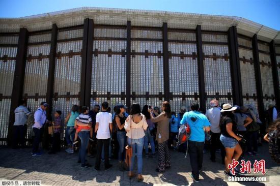 资料图:美墨边境临时短暂开放,在美国加州圣迭戈一侧的人们排队等待与亲人见面。